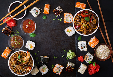 camaron: Tradicional comida japonesa - sushi, rollos, arroz con fideos udon con camarones y pollo y setas sobre un fondo oscuro. Vista superior