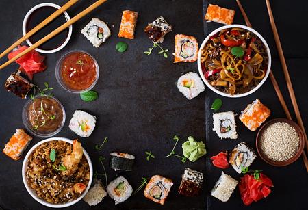 Tradicional comida japonesa - sushi, rollos, arroz con fideos udon con camarones y pollo y setas sobre un fondo oscuro. Vista superior