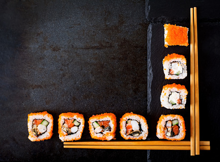 sushi menu: Traditional Japanese food - sushi, rolls and chopsticks for sushi on a dark background. Top view