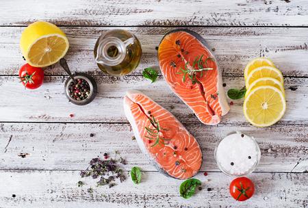 Trancio di salmone crudo e verdure per la cottura su uno sfondo di legno chiaro in stile rustico. Vista dall'alto Archivio Fotografico - 50363261
