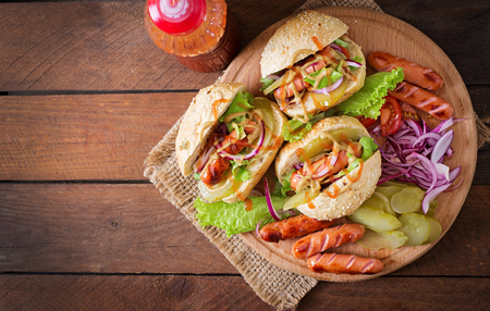 hotdog sandwiches: Hot dog - sandwich with pickles, red onions and lettuce on wooden background. Top view