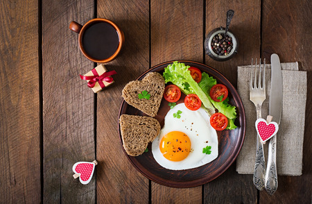 colazione: Colazione a San Valentino - uova e pane fritto in forma di un cuore e verdure fresche. Vista dall'alto