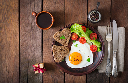 english food: Breakfast on Valentines Day - fried eggs and bread in the shape of a heart and fresh vegetables. Top view