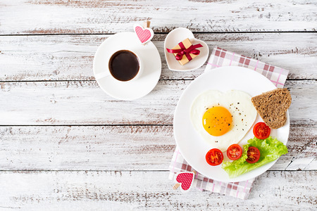 morning coffee: Breakfast on Valentines Day - fried eggs and bread in the shape of a heart and fresh vegetables. Top view