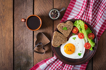 'english: Breakfast on Valentines Day - fried eggs and bread in the shape of a heart and fresh vegetables. Top view
