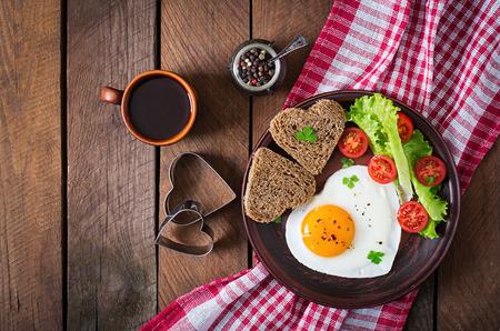 Desayuno en el Día de San Valentín - los huevos y el pan frito en la forma de un corazón y verduras frescas. Vista superior