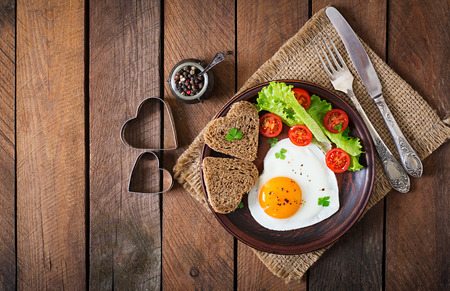 Breakfast on Valentine's Day - fried eggs and bread in the shape of a heart and fresh vegetables. Top view Imagens - 50363442