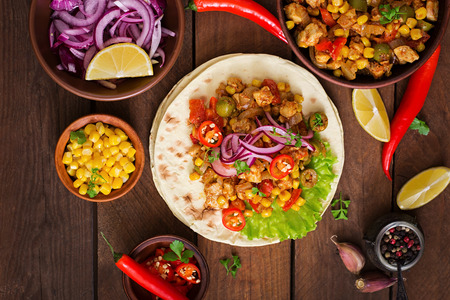 meal preparation: Mexican tacos with meat, corn and olives on wooden background. Top view Stock Photo