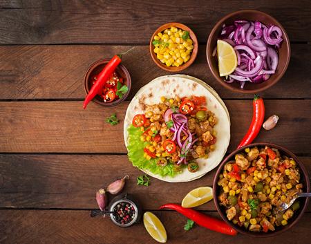 tortilla de maiz: Tacos mexicanos con carne, maíz y aceitunas en el fondo de madera. Vista superior