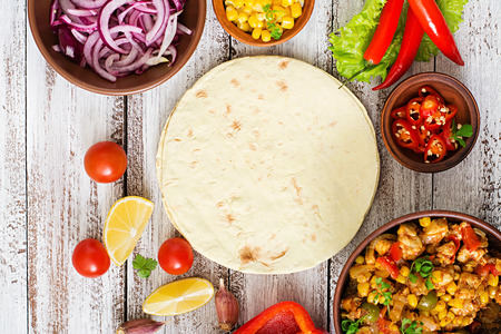 Ingredients for Mexican tacos with meat, corn and olives on wooden background. Top view Standard-Bild
