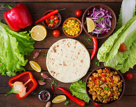 Ingredients for Mexican tacos with meat, corn and olives on wooden background. Top view 免版税图像
