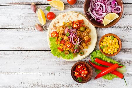 Tacos mexicanos con carne, maíz y aceitunas en el fondo de madera. Vista superior Foto de archivo