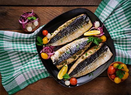 Gebackene Makrele mit Kräutern und garniert mit Zitrone und eingelegtem Gemüse. Draufsicht