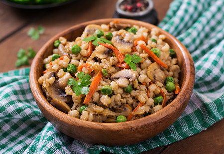 perlas: Vegetariana desmenuzable perla gachas de cebada con setas y guisantes verdes en un cuenco de madera