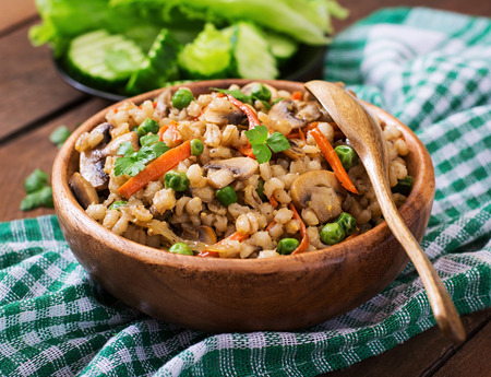 crumbly: Vegetarian crumbly pearl barley porridge with mushrooms and green peas in a wooden bowl