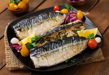 Baked mackerel with herbs and garnished with lemon and pickled vegetables 免版税图像