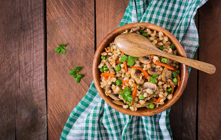 crumbly: Vegetarian crumbly pearl barley porridge with mushrooms and green peas in a wooden bowl. Top view Stock Photo