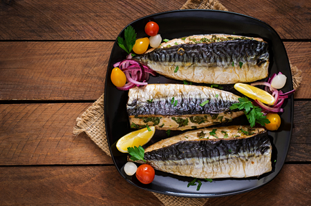 fish plate: Baked mackerel with herbs and garnished with lemon and pickled vegetables. Top view Stock Photo