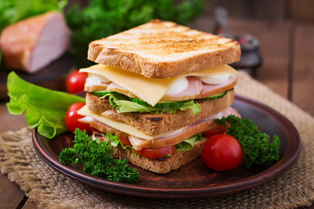 Club sandwich with cheese, cucumber, tomato, ham and eggs. 版權商用圖片 - 52913579