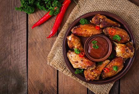 Savanyú-édes sült csirke szárny és sauce.Top nézet