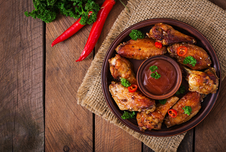 american cuisine: Sour-sweet baked chicken wings and sauce.Top view