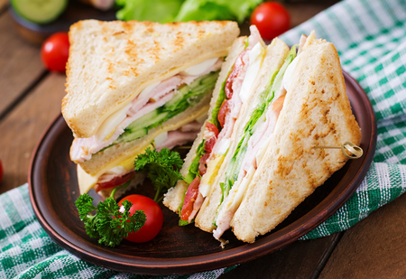 sandwich: Club sandwich with cheese, cucumber, tomato, ham and eggs.