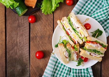 food dressing: Club sandwich with cheese, cucumber, tomato, ham and eggs. Top view