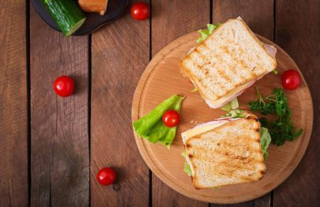 bocadillo: Club sándwich con queso, pepino, tomate, jamón y huevos. Foto de archivo