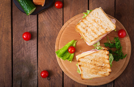slices of bread: Club sandwich with cheese, cucumber, tomato, ham and eggs.