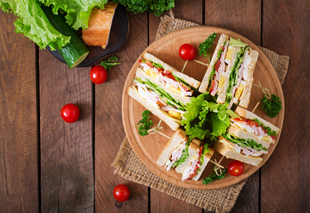 Club sandwich with cheese, cucumber, tomato, ham and eggs. Top view Imagens - 52913765