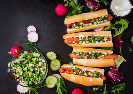 hot sauce: Healthy Hot Dog dressed with yogurt and cucumber salsa with radishes on dark backgroud. Top view