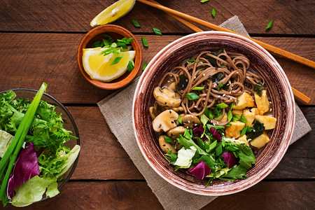 Miso and soba noodle soup with roasted tofu and mushrooms. Top view