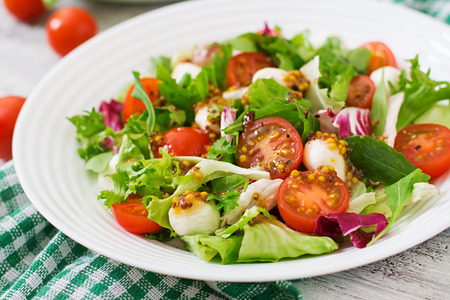 dietary: Dietary salad with tomatoes, mozzarella lettuce with honey-mustard dressing Stock Photo