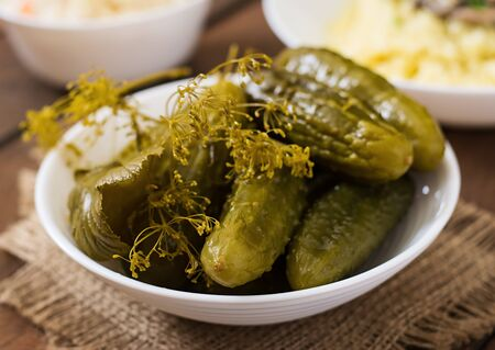 marinated gherkins: Pickled cucumbers on a dark wooden background.