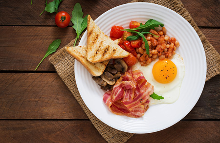 english food: English breakfast - fried egg, beans, tomatoes, mushrooms, bacon and toast. Top view
