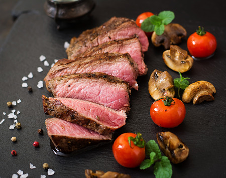 steak grill: Juicy steak medium rare beef with spices and grilled vegetables.