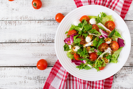 Dietary salad with tomatoes, mozzarella lettuce with honey-mustard dressing. Top view Stockfoto