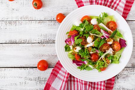 Sałatka dietetyczna z pomidorów, mozzarella sałata z dressingiem miodowo-musztardowym. Widok z góry