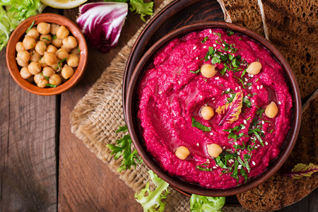 Roasted Beet Hummus with toast in a ceramic bowl on a wooden background. Top view 免版税图像