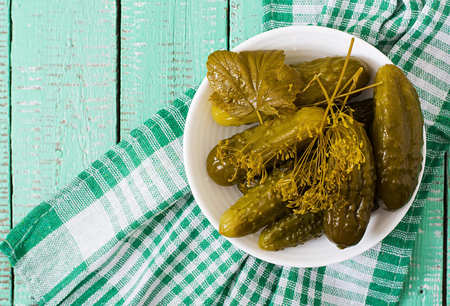marinated gherkins: Pickled cucumbers on a light wooden background. Top view