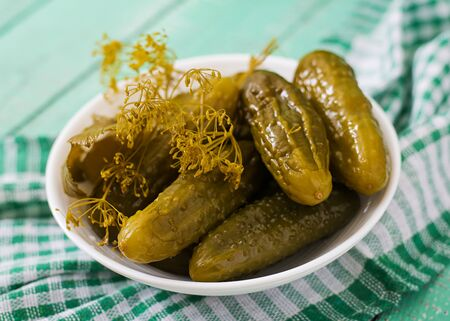 marinated gherkins: Pickled cucumbers on a light wooden background