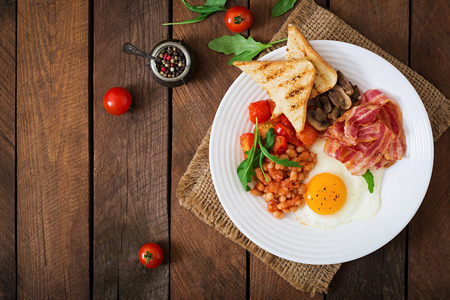 beans on toast: English breakfast - fried egg, beans, tomatoes, mushrooms, bacon and toast. Top view