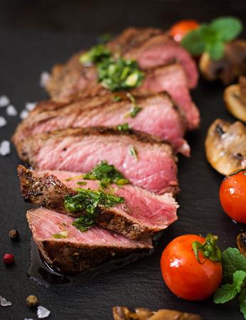 carne asada: jugoso filete medio raro carne con especias y verduras asadas. Foto de archivo