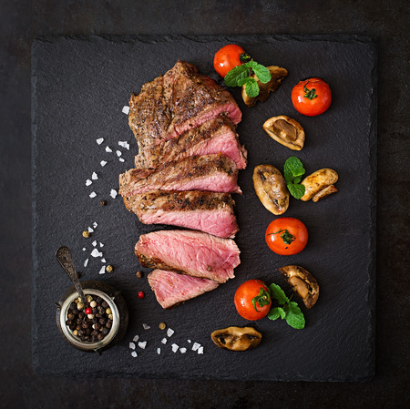 bbq background: Juicy steak medium rare beef with spices and grilled vegetables. Top view