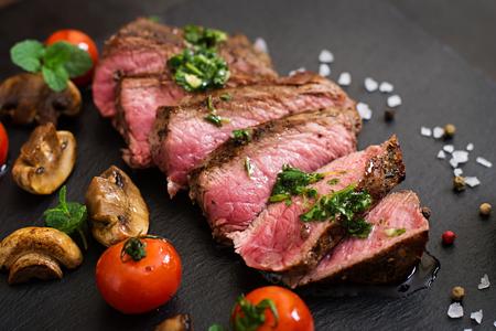 Saftiges Steak medium rare Rindfleisch mit Gewürzen und gegrilltem Gemüse. Lizenzfreie Bilder