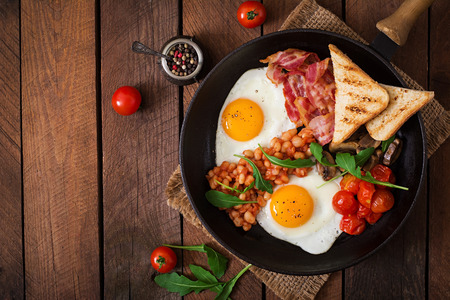 american cuisine: English breakfast - fried egg, beans, tomatoes, mushrooms, bacon and toast. Top view