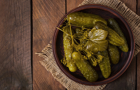 marinated gherkins: Pickled cucumbers on a dark wooden background. Top view Stock Photo