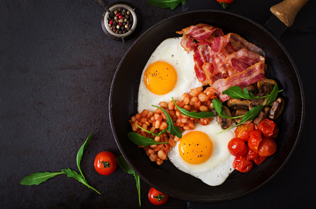 english breakfast: English breakfast - fried egg, beans, tomatoes, mushrooms, bacon and toast. Top view
