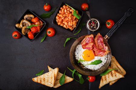Englisch Frühstück - Spiegelei, Bohnen, Tomaten, Champignons, Speck und Toast. Aufsicht