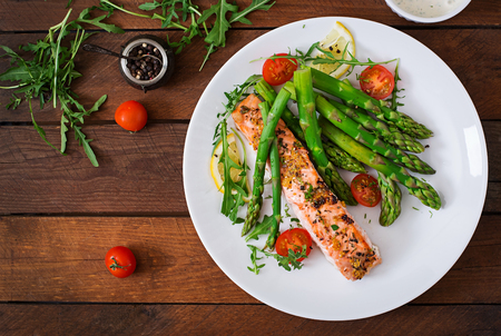 Baked salmon garnished with asparagus and tomatoes with herbs. Top view Stockfoto